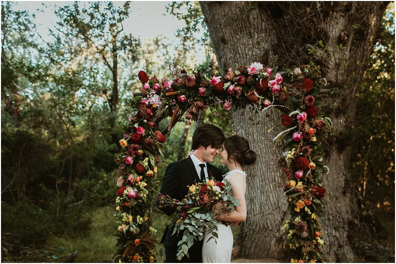 bridal couple infront of flowers